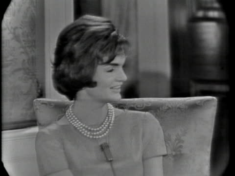 medium shot of jacqueline kennedy, who is sitting on a chair, and wearing a dress and pearl necklace. she has short hair and a microphone hung around... - dress stock videos & royalty-free footage