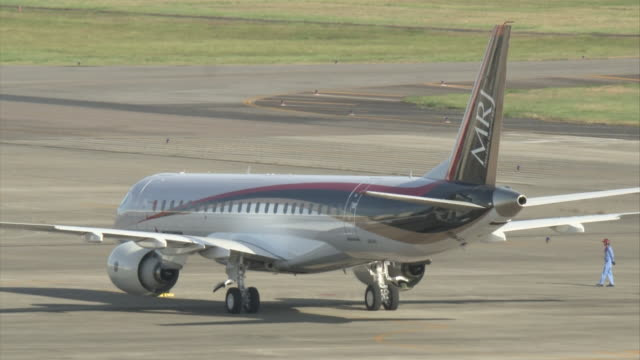 "stockvideo's en b-roll-footage met medium shot of japan's first domestically produced commercial passenger aircraft for 50 years ""mitsubishi regional jet "" staying at the runway of... - start en landingsbaan"