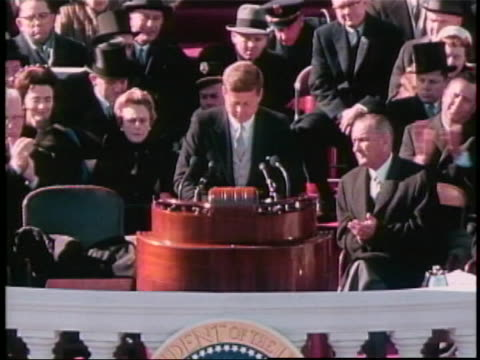 medium shot of jfk standing at lectern with lyndon b. johnson and others seated behind him. he alternates between looking at his speech and looking... - john f. kennedy us president stock videos & royalty-free footage