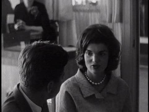 medium shot of john f. kennedy and jacquline kennedy sitting at a long dining table in a diner. shot shows john's face and jackie's side and back, as... - jackie kennedy stock videos & royalty-free footage