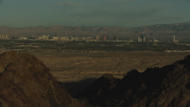 stockvideo's en b-roll-footage met medium shot of las vegas appearing from behind the frenchman mountain at sunrise - fysische geografie