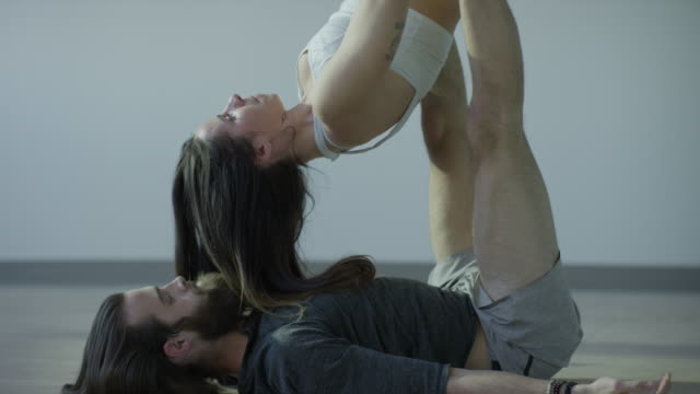 Medium shot of laughing couple practicing acro yoga in studio / Orem, Utah, United States
