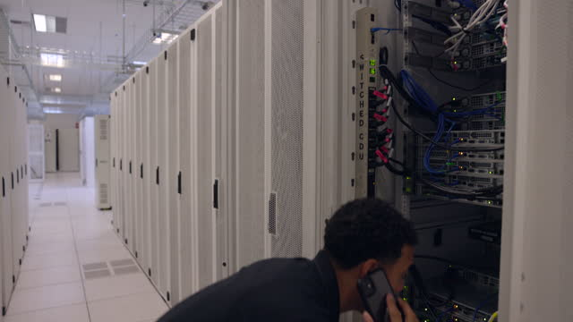medium shot of male it professional looking into server rack while holding laptop and talking on phone in data center - computer network stock videos & royalty-free footage