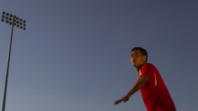 Medium shot of male soccer player kicking high ball