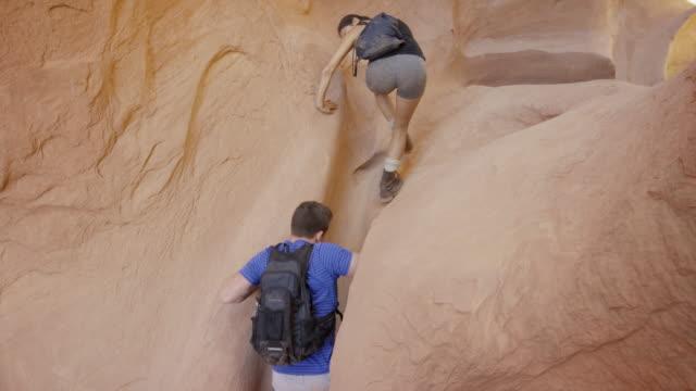 medium shot of man and woman climbing in narrow slot canyon / escalante, utah, united states - slot canyon stock videos & royalty-free footage