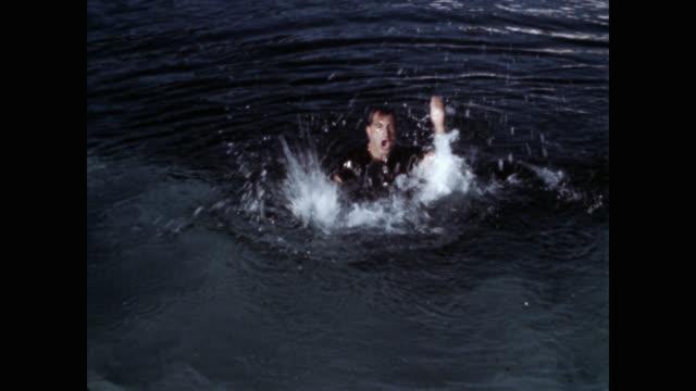 medium shot of man drowning in lake - drowning stock videos & royalty-free footage