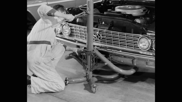 medium shot of man lifting car with car jack in workshop - automobile industry stock videos & royalty-free footage