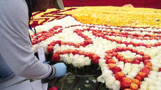 vidéos et rushes de medium shot of man manually placing roses on flower arreangement - composition florale
