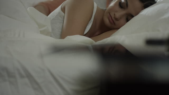 Medium shot of man massaging back of woman in bed / Cedar Hills, Utah, United States