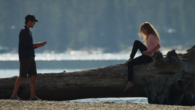 Medium shot of man photographing girlfriend on log at lake / Redfish Lake, Idaho, United States