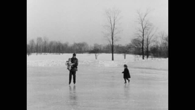 medium shot of man playing with his daughters on ice rink in winter, michigan, usa - four people stock videos & royalty-free footage