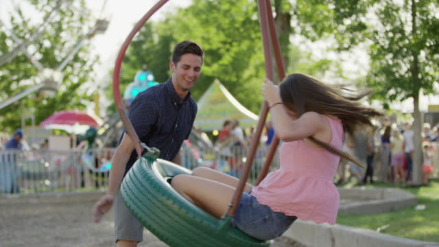 medium shot of man spinning woman on tire swing at amusement park / pleasant grove, utah, united states - tire swing stock videos & royalty-free footage
