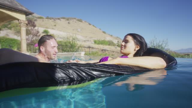 Medium shot of man surprising woman in swimming pool / Cedar Hills, Utah, United States