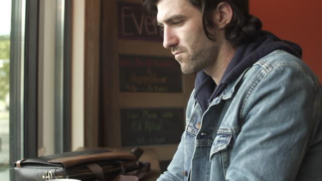 vídeos de stock, filmes e b-roll de medium shot of man using a laptop in a coffee shop - jaqueta jeans