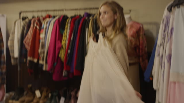 stockvideo's en b-roll-footage met medium shot of man watching playful woman shopping for vintage clothes / provo, utah, united states - provo