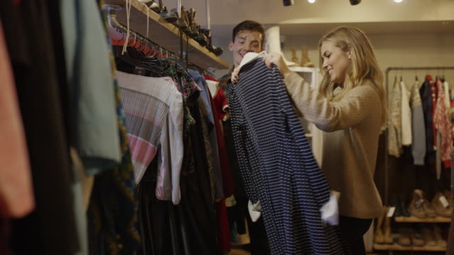 stockvideo's en b-roll-footage met medium shot of man watching woman shopping for vintage dress / provo, utah, united states - provo