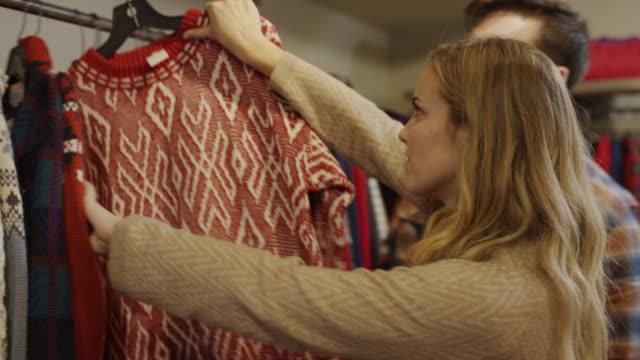Medium shot of man watching woman shopping for vintage sweater / Provo, Utah, United States