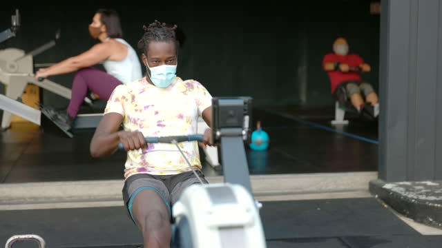 medium shot of man wearing protective face mask working out on rowing machine at outdoor gym - 50 59 years stock videos & royalty-free footage