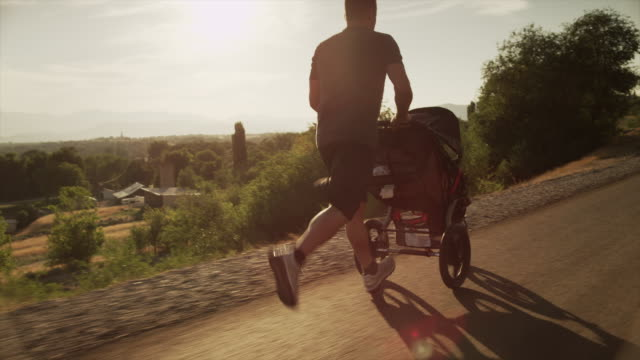 medium shot of man with baby carriage running on sunny road / cedar hills, utah, united states - sportkinderwagen stock-videos und b-roll-filmmaterial