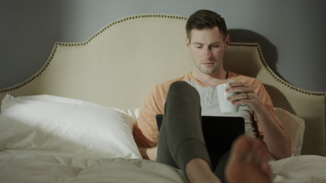 medium shot of man with coffee using digital tablet on bed / cedar hills, utah, united states - tracksuit bottoms stock videos & royalty-free footage