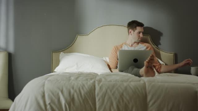 Medium shot of man with coffee using laptop on bed / Cedar Hills, Utah, United States