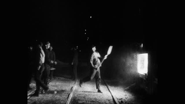 medium shot of manual workers throwing coal in furnace in steel factory - human age stock videos & royalty-free footage