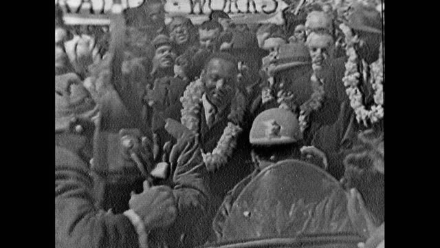 medium shot of martin luther king, ralphe bunche and ralph abernathy leading the march from selma to montgomery wearing floral lei garlands; 21st... - smiling stock videos & royalty-free footage