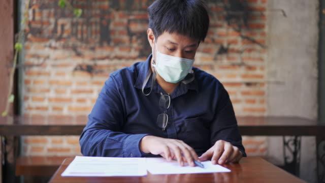 米国の不在者投票投票を調べる覆面ぽっちゃりしたアジア人男性のミディアムショット - 米民主党点の映像素材/bロール