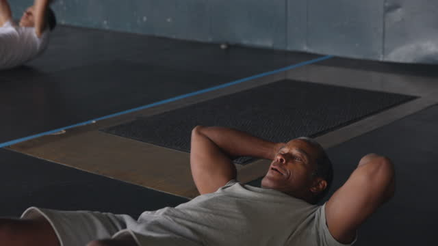 medium shot of mature man doing sit ups while working out in gym - mature men stock videos & royalty-free footage