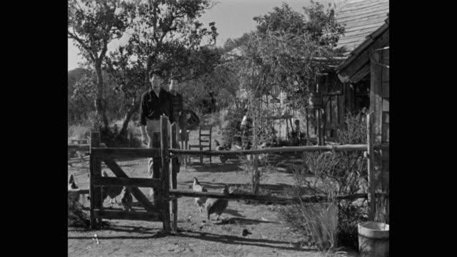 medium shot of men standing near fence - 牧夫点の映像素材/bロール