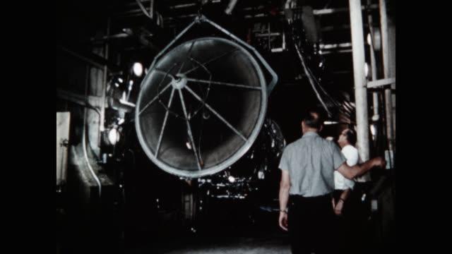 stockvideo's en b-roll-footage met medium shot of men working in aircraft assembly plant - drukknop