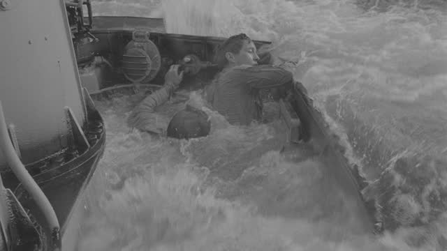 medium shot of military personnel crouching on deck of submarine as waves overtake them and submarine submerging in sea - 50 seconds or greater stock videos & royalty-free footage