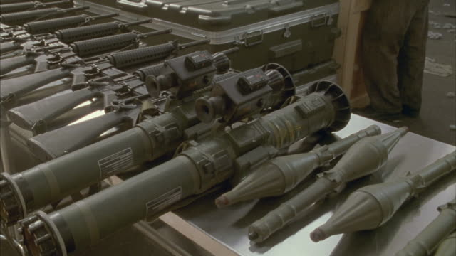 Medium shot of military weapons lined up on a table.