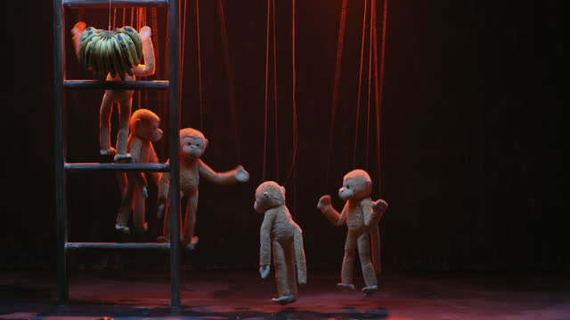 medium shot of monkey puppets trying to catch bananas hanging on wooden ladder in rain during puppet show - puppet stock videos & royalty-free footage