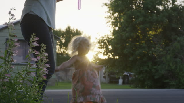 medium shot of mother and daughter blowing bubbles outdoors / orem, utah, united states - orem utah stock videos & royalty-free footage