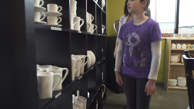 vídeos de stock e filmes b-roll de medium shot of mother and daughter in a ceramic studio - cristaleira