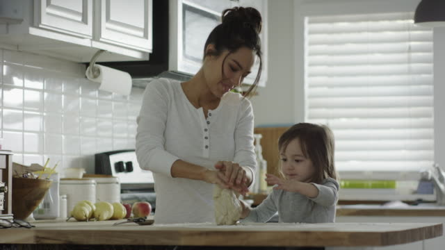 Medium shot of mother and daughter kneading dough in kitchen / Provo, Utah, United States