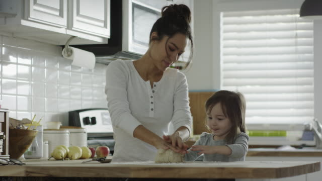 medium shot of mother and daughter kneading dough in kitchen / provo, utah, united states - provo stock videos & royalty-free footage