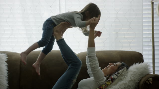 stockvideo's en b-roll-footage met medium shot of mother and daughter playing on sofa / provo, utah, united states - provo