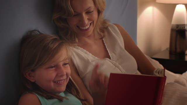 vídeos de stock e filmes b-roll de medium shot of mother and daughter reading in bed/marbella region, spain - lâmpada elétrica