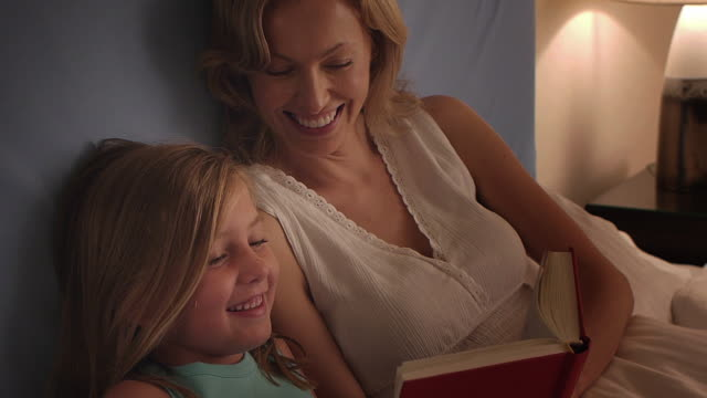 Medium shot of mother and daughter reading in bed/Marbella region, Spain