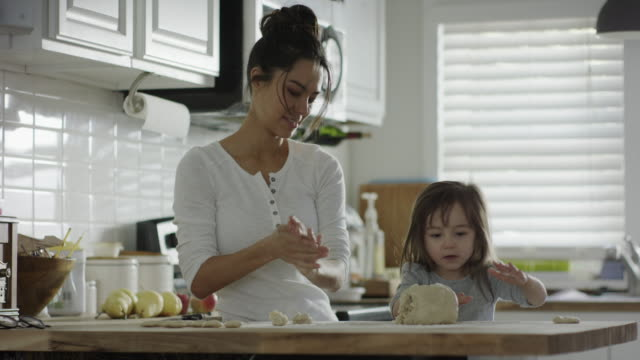 medium shot of mother and daughter rolling dough in kitchen / provo, utah, united states - provo stock videos & royalty-free footage
