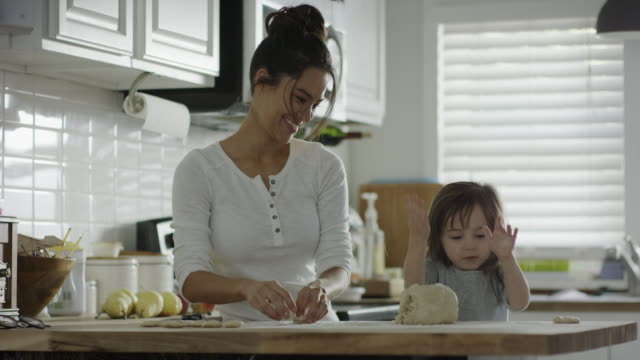 medium shot of mother and daughter rolling dough in kitchen / provo, utah, united states - provo stock-videos und b-roll-filmmaterial
