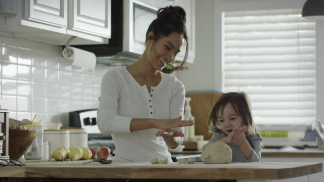 Medium shot of mother and daughter rolling dough in kitchen / Provo, Utah, United States