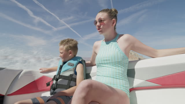 medium shot of mother and son riding in speedboat on lake / lake powell, utah, united states - flytväst bildbanksvideor och videomaterial från bakom kulisserna