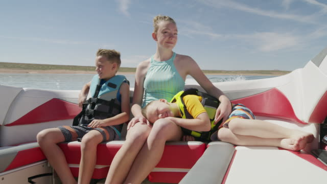 medium shot of mother and sons riding in speedboat on lake / lake powell, utah, united states - flytväst bildbanksvideor och videomaterial från bakom kulisserna