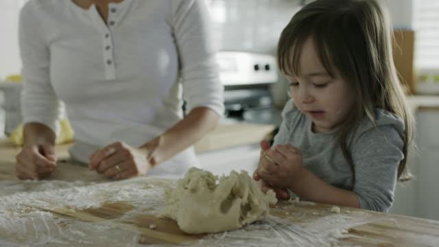 Medium shot of mother and teaching daughter baking in kitchen / Provo, Utah, United States