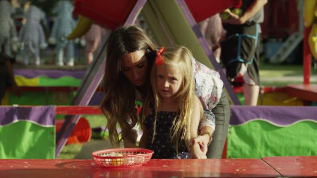 vídeos de stock e filmes b-roll de medium shot of mother helping daughter play game at carnival / american fork, utah, united states - fotografia de três quartos