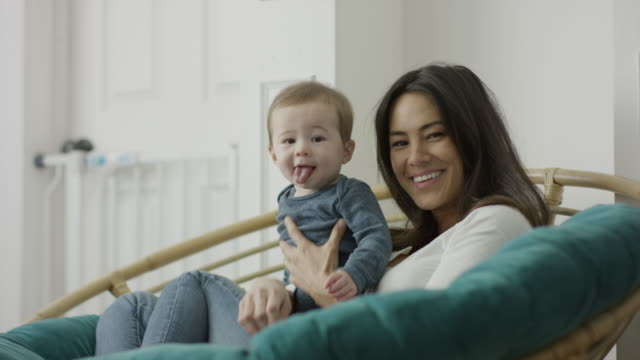 stockvideo's en b-roll-footage met medium shot of mother sitting holding baby son with tongue out / provo, utah, united states - provo