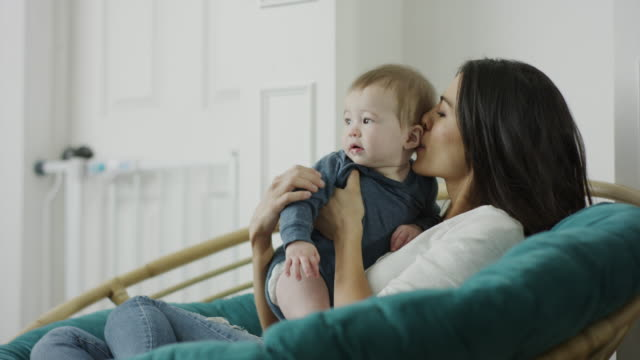 stockvideo's en b-roll-footage met medium shot of mother sitting in papasan chair whispering to baby son / provo, utah, united states - provo